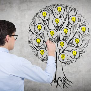 Rear view of young professional who is drawing a tree with light bulbs on the concrete wall. Light bulbs as a concept of new business ideas.
